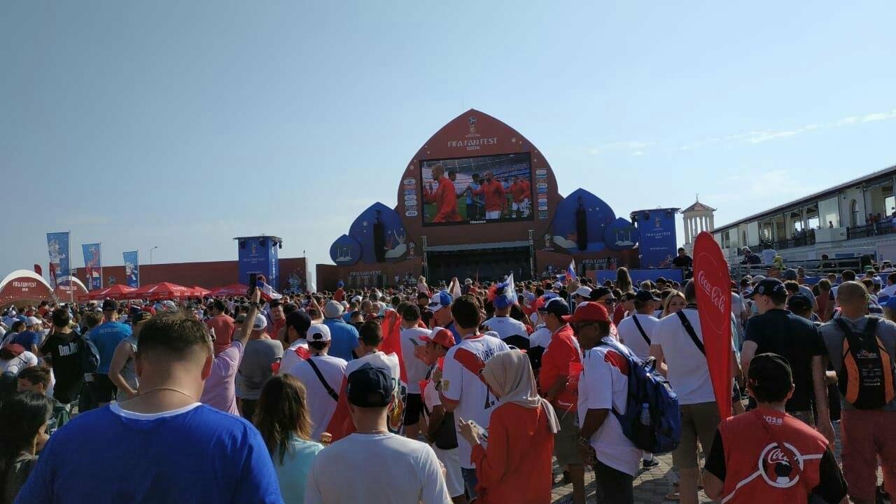 Болельщики из разных стран, собравшиеся на территории проведения Фестиваля болельщиков  FIFA в Сочи, напряжённо наблюдают за прямой трансляцией хода матча по размещенному на возвышении видеомонитору. Территория Южного мола морского порта города Сочи